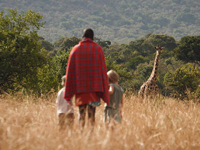 Mara Maasai guide takes children on a walking safari.