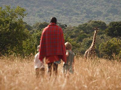 Mara Maasai guide takes children on a walking safari.