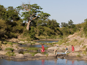Guests and guides crossing the Mara River during a walking safari.