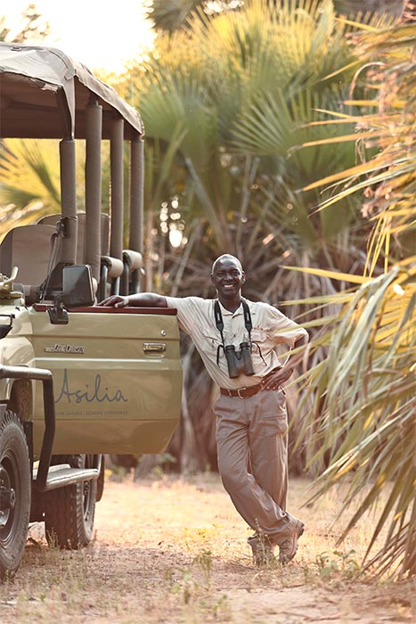 guide surrounded by palms ready to take you on your game drive