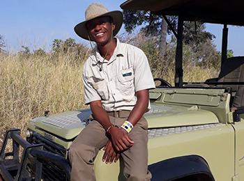 Kwihala Camp Guide sitting on safari vehicle