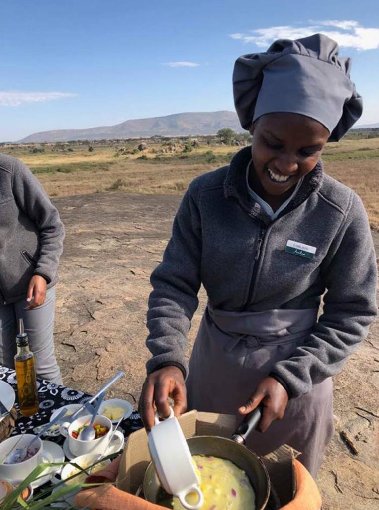 Lailatu, one of our chefs at Dunia Camp, prepares an omelette while having breakfast in the Serengeti.