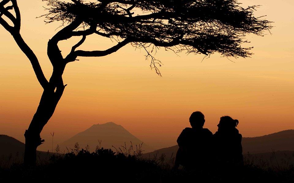 couple watching the sunrise on safari in africa