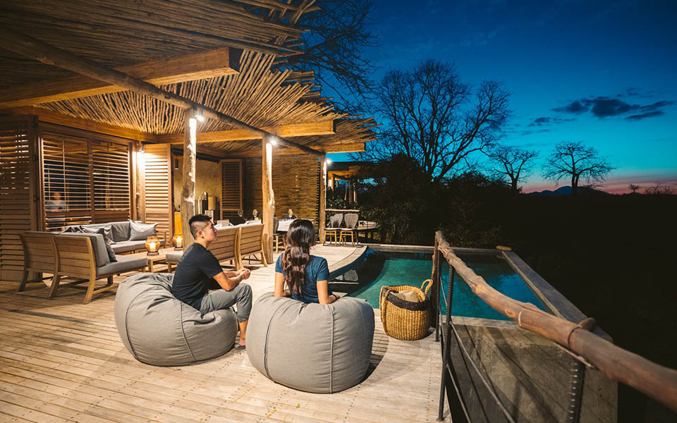 Couple enjoying sunset by the pool at luxury accommodation in africa